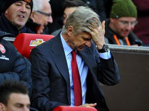 Arsene Wenger runs his fingers through his hair in frustration