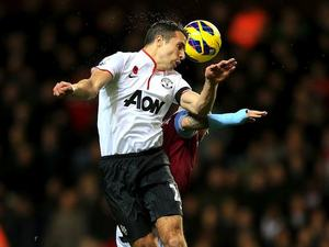 Robin van Persie jumps to head the ball