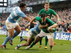 Ireland's Jonathan Sexton skips past Argentina's Eusebio Guinazu and Martin Landajo to score a try on November 24, 2012