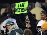 "A Philadelphia Eagles fan holds up a ""Fire Andy Reid"" sign on November 26, 2012"