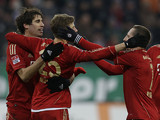 Bayern Munich's Thomas Mueller is congratulated by his team mates after scoring the opener on December 8, 2012
