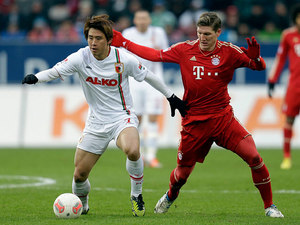 Augsburg's Koo Ja-cheol and Bayern Munich's Bastian Schweinsteiger battle for the ball on December 8, 2012