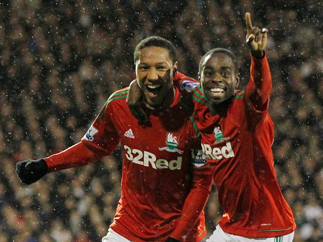 Jonathan de Guzman is congratulated by team mate Nathan Dyer after scoring his team's second goal on December 29, 2012