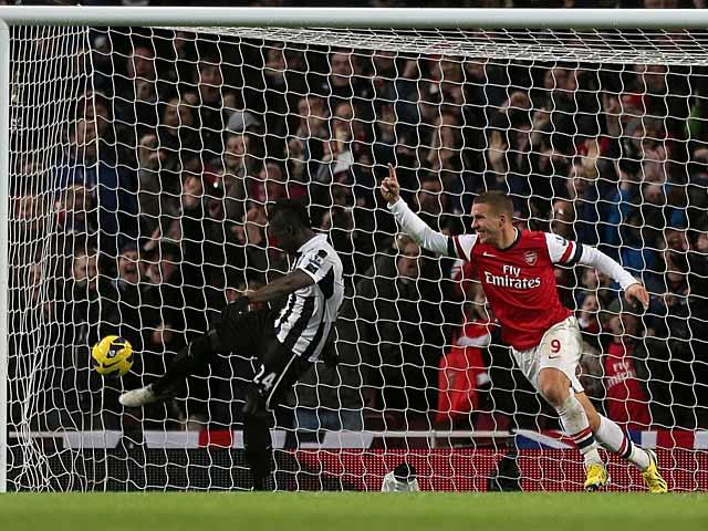 Lukas Podolski celebrates scoring his team's third goal on December 29, 2012