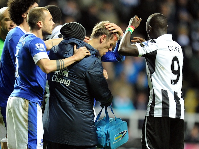 Players from both sides check on Phil Neville after he cut his head during the game between Everton and Newcastle on January 2, 2013