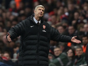 Arsenal boss Arsene Wenger stands dejected after the sending off of Laurent Koscielny against Man City on January 13, 2013