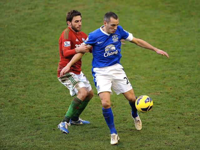 Everton midfielder Leon Osman battles with Swansea's Angel Rangel during the game on January 12, 2013