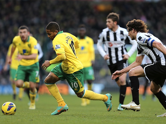 Norwich striker Simeon Jackson turns away from Newcastle's Fabricio Coloccini on January 12, 2013