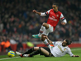 Chico Flores and Theo Walcott battle for the ball during the FA Cup third round replay on January 16, 2013