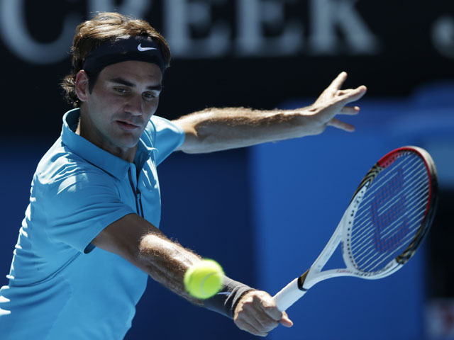 Roger Federer makes a backhand return in his first round match against Benoit Paire at the Australian Open tennis championship on January 15, 2013