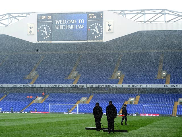 Groundstaff at White Hart Lane clear the snow from the pitch ahead of the match against Manchester United on January 20, 2013