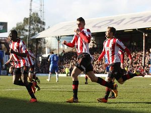 Brentford's Marcello Trotta celebrates with team mates after scoring the opening goal in the FA Cup fourth round tie with Chelsea on January 27, 2013