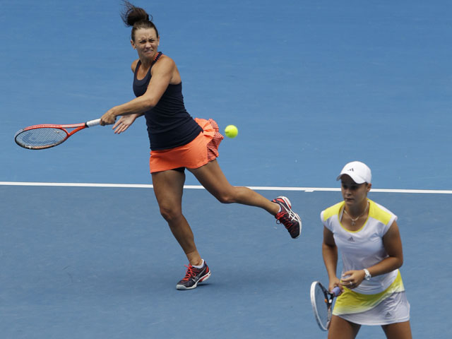 Caseu Dellacqua of Australia hits the ball past partner Ashleigh Barty during the women's doubles final at the Australian Open tennis championship on January 25, 2013