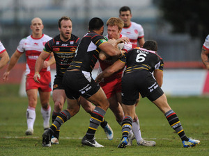 Hull KR's David Hodgson is tackeled by two Catalan Dragons in their match on February 3, 2013
