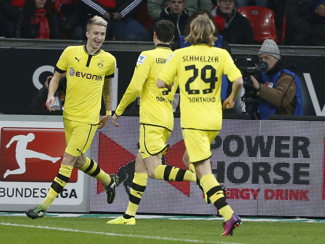 Borussia Dortmund player Marco Reus celebrates with teammates after scoring on February 3, 2013