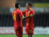 Wales player Gareth Bale celebrates with a teammate after scoring his side's opening goal on February 6 , 2013