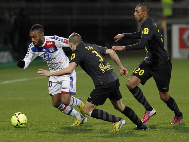 Lyon's Alexandre Lacazette tries to dribble the ball past two Lille players druing their match on February 10, 2013