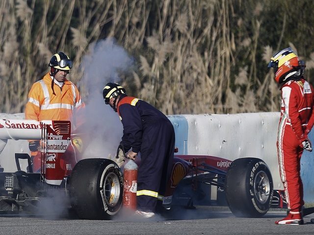 Ferrari development Pedro de la Rosa watches track marshals tend to his car after a fire on February 8, 2013