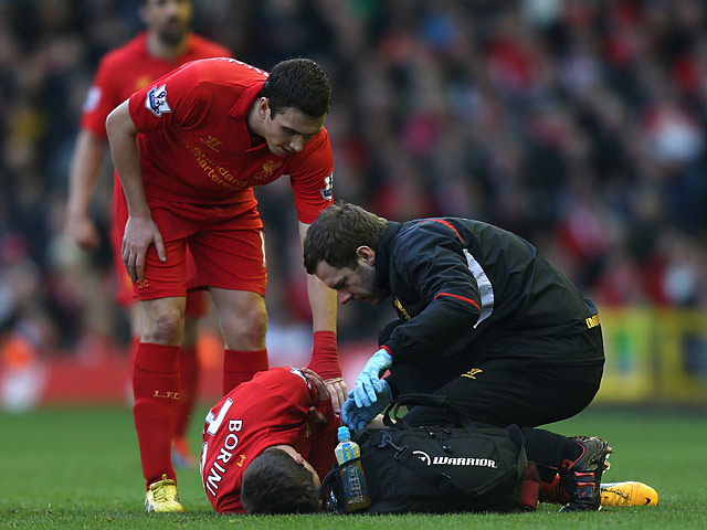 Stewart Downing checks on team mate Fabio Borini as he is attended to by the physio after picking up an injury during the match against Swansea on February 17, 2013