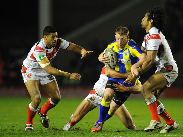 Warrington Wolves' Chris Riley is tackled by St Helens players during the Super League clash on March 8, 2013