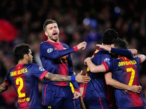 Barcelona players celebrate the opening goal in their Champions League clash against AC Milan on March 12, 2013
