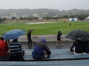 Spectators shelter as rain falls during day four of the Second Test match between New Zealand and England on March 17, 2013