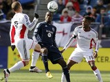 Kansas City's  C.J. Sapong battles for the ball with New England Revolution's Chad Barrett during the MLS match on March 23, 2013