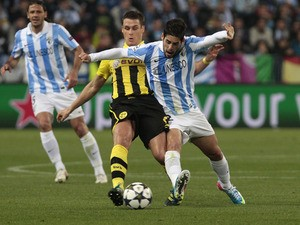 Malaga's Isco is challenged by Dortmund's Sebastian Kehl during the Champions League match on April 3, 2013