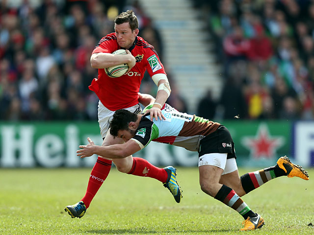 Munster's Dennis Hurley is tackled by Harlequins' George Lowe on April 7, 2013