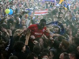 Cardiff City's Leon Barnett is carried by fans after winning promotion to the Premier League on April 16, 2013