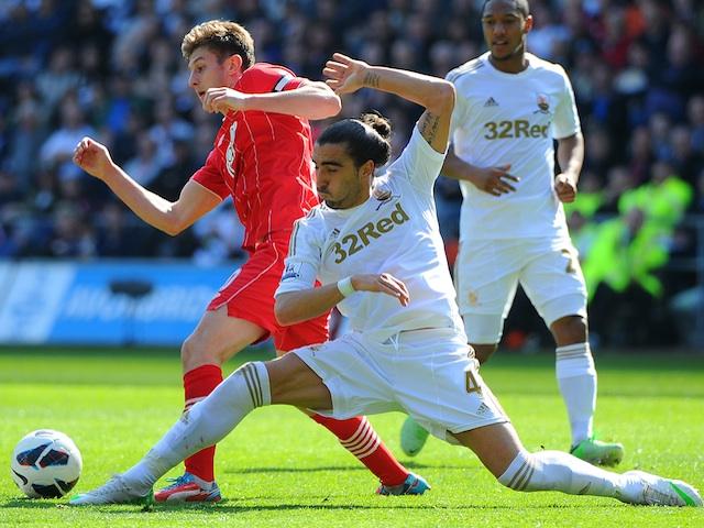 Swansea defender Chico tackles Saints' skipper Adam Lallana on April 20, 2013