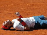 Rafael Nadal from Spain falls to the ground in celebration after winning the final of the Madrid Masters on May 12, 2013