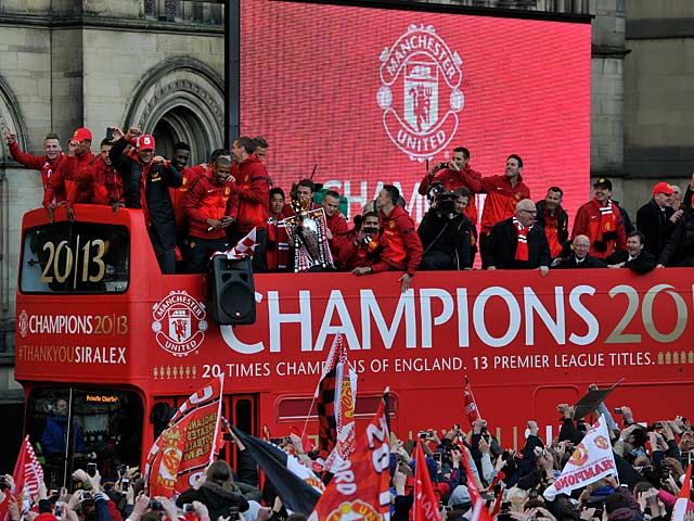 Manchester United players and staff celebrate on the bus during the winners parade on May 13, 2013