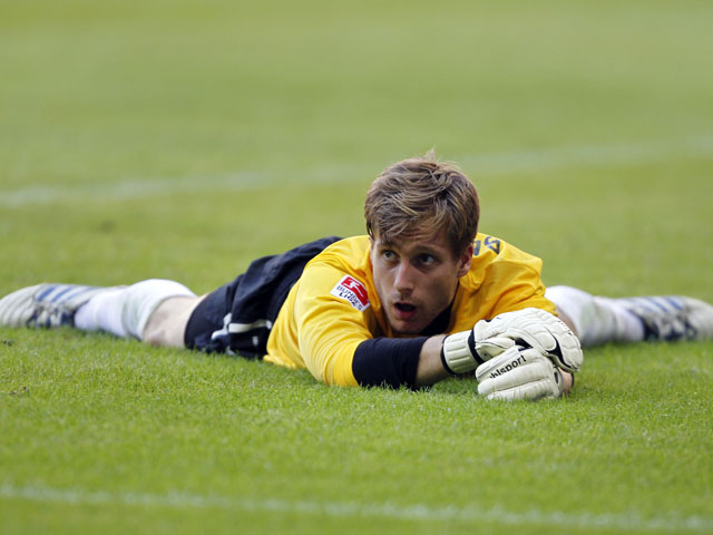 Freiburg's goalkeeper Oliver Baumann lies on the pitch during the Bundesliga clash with Bayern Munich on September 10, 2011