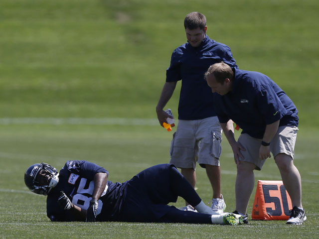 Seattle Seahawks team personnel attend to Seahawks' Anthony McCoy during a training session on May 20, 2013