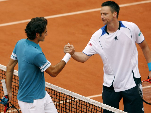 Roger Federer and Robin Soderling meet at the net after their French Open clash.