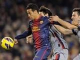 Barcelona attacker Thiago holds off two challenges.