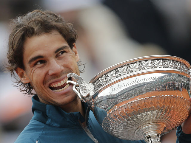 Spain's Rafael Nadal bites the trophy after beating compatriot David Ferrer in the French Open final on June 9, 2013