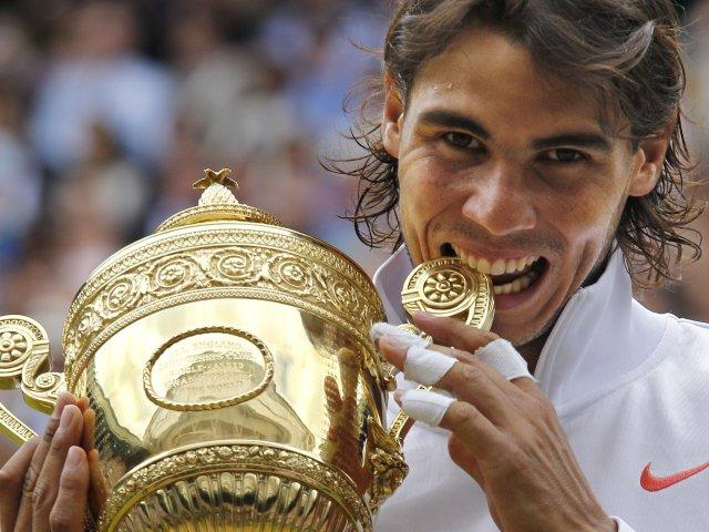 Rafael Nadal celebrates with the Wimbledon trophy.
