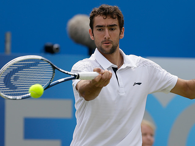Marin Cilic returns the ball to Tomas Berdych during their quarter final match at Queens on June 14, 2013