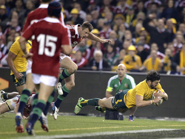 Australia's Adam Ashley-Cooper dives over to score a try against the British and Irish Lions during their rugby union test match on June 29, 2013