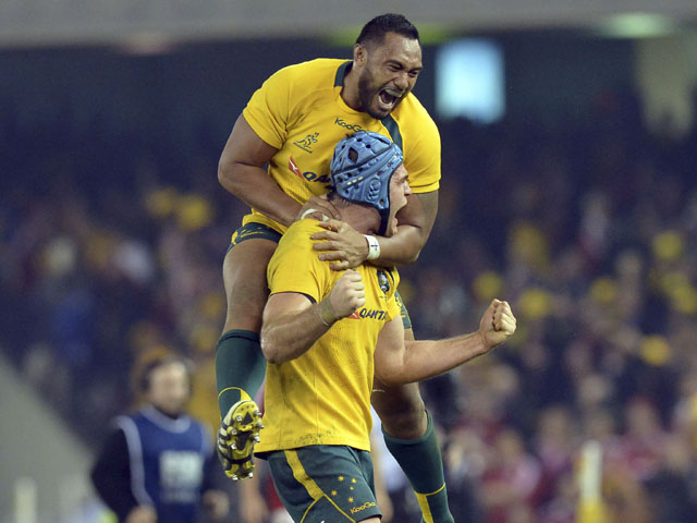 Australia's Sekope Kepu leaps onto James Horwill, front, as they celebrate beating the British and Irish Lions' during their rugby union test match on June 29, 2013
