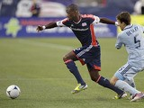 New England Revolution forward Dimitry Imbongo moves the ball past Sporting Kansas City defender Matt Besler during a MLS match on August 4, 2012