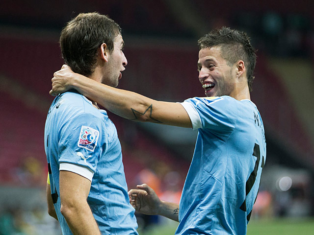 Uruguay's Nicolas Lopez is congratulated by team mate Gaston Silva after scoring the opening goal against Nigeria during the U20 World Cup on July 2, 2013