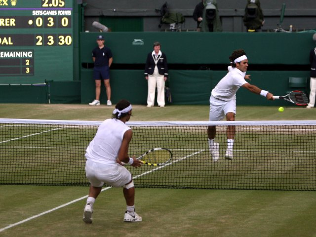 Roger Federer and Rafael Nadal exchange shots at the net during the 2008 Wimbledon final.