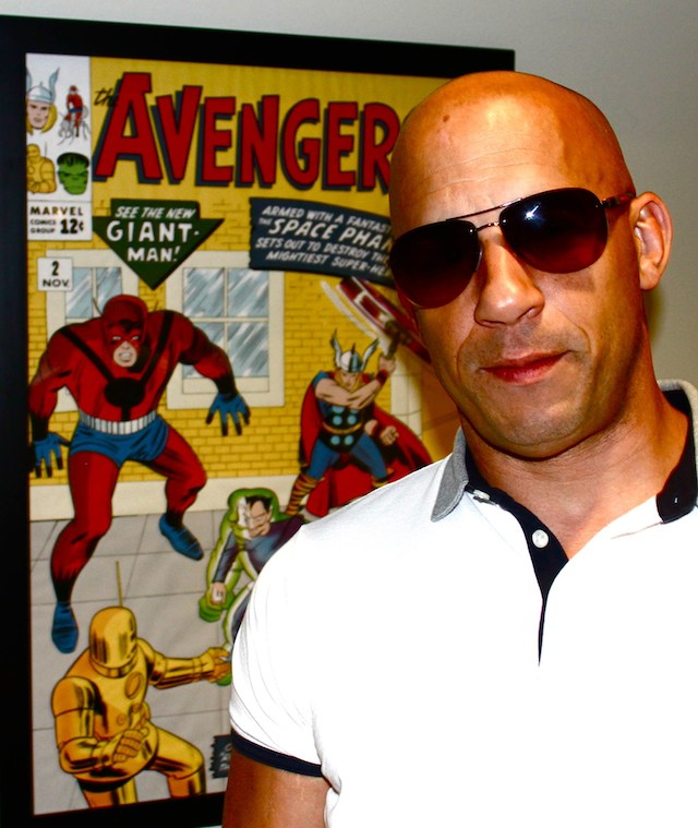 Vin Diesel standing in front of a Marvel poster (640w)