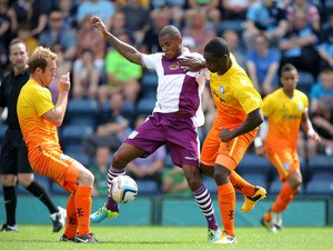 Aston Villa's Leandro Bacuna battles for possession of the ball with Wycombe Wanderers' Anthony Stewart and Stuart Lewis during the friendly match on July 20, 2013