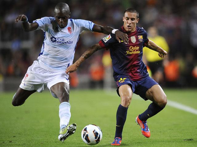 Granada's Allan Nyom battles with Barcelona's Tello during the LA Liga match on September 22, 2012