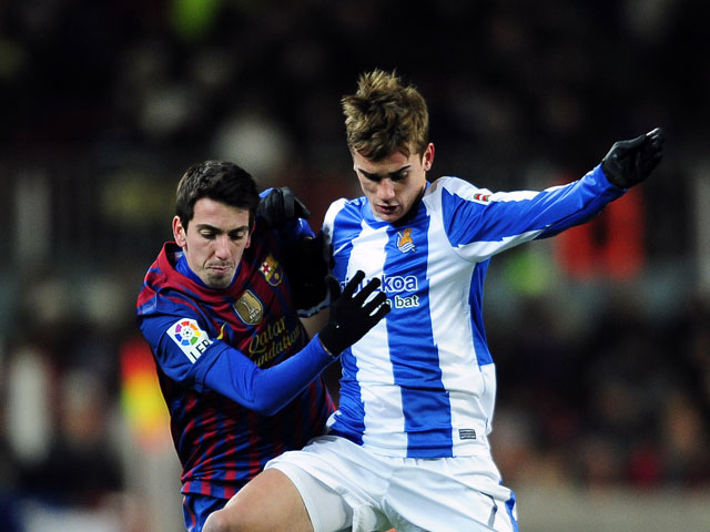 Real Sociedad's Antoine Griezmann challenges for the ball with FC Barcelona's Cuenca during the match on February 4, 2012