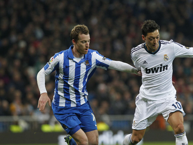 Real Sociedad's David Zurutuza vies for the ball with Real Madrid's Mesut Ozil during the La Liga clash on January 6, 2013
